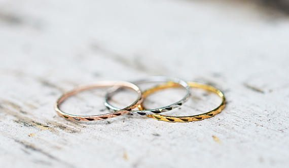 A unique set of three 1mm stackable rings, one each in 18k rose gold, 18k white gold, and 18k yellow gold, all plated over stainless steel. The rings are texturized to give a soft wave design on the outside, the inside band is smooth to the skin. The gold is bonded to the base metal 5 times over, and is not quick to fade. The rings are not attached to each other, so you can wear one at a time, or stack to your liking. This is a set and the price is for all three rings pictured. Jewellery…