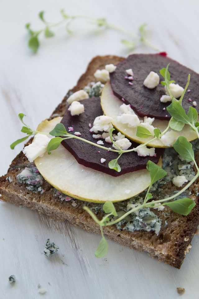 open faced red beet, pear and blue cheese sandwich on dark rye.