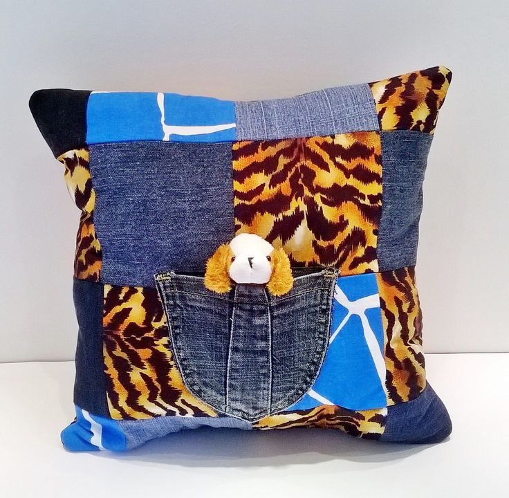 Dog cushion is made out of denim and cotton fabric.  I have machine sewn a denim pocket in the centre of the cushion.  There is a removable dog cuddly toy in the pocket.