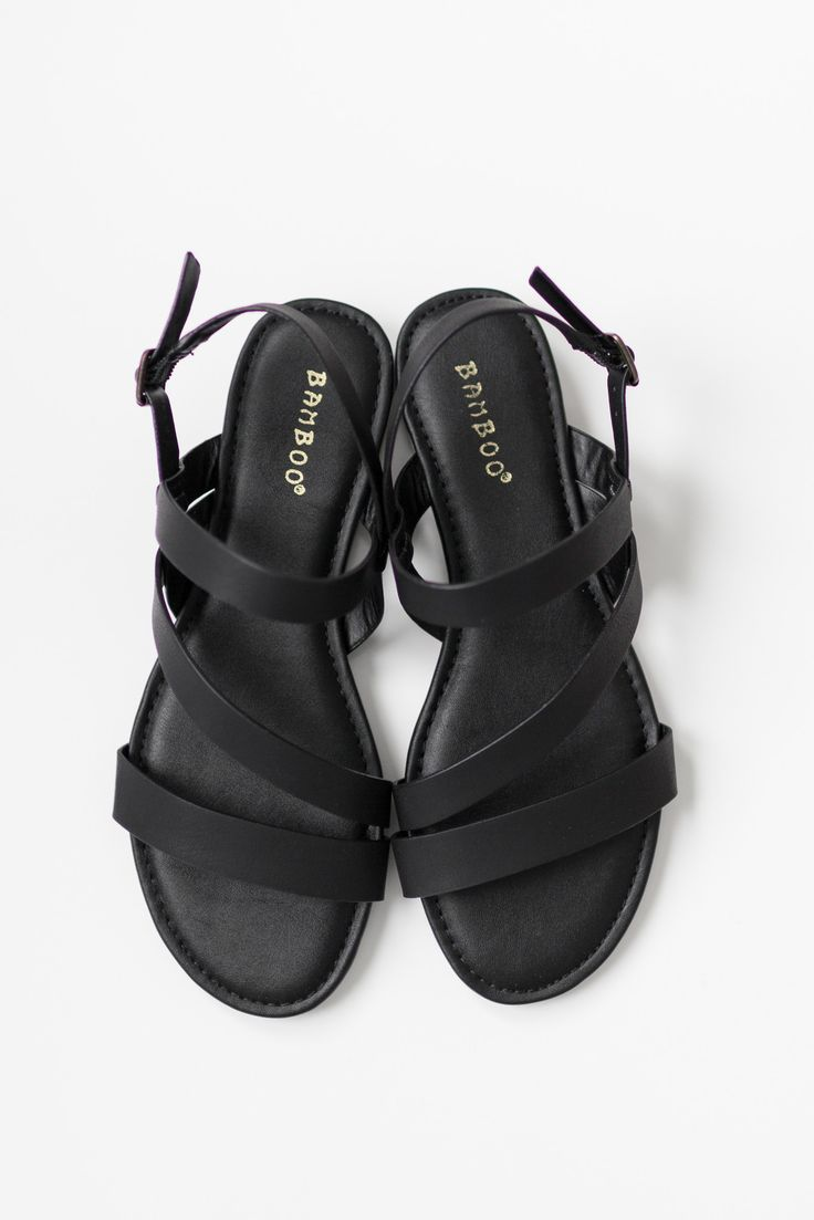 """- Black flat sandals with a strappy faux leather upper - Small .75"""" back heel - Buckle closure around ankle - Lightly padded insole - True to US size - All man made material - Imported"""