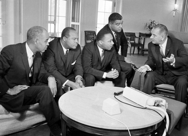 President Lyndon B. Johnson, right, talks with civil rights leaders in his White House office in Washington.