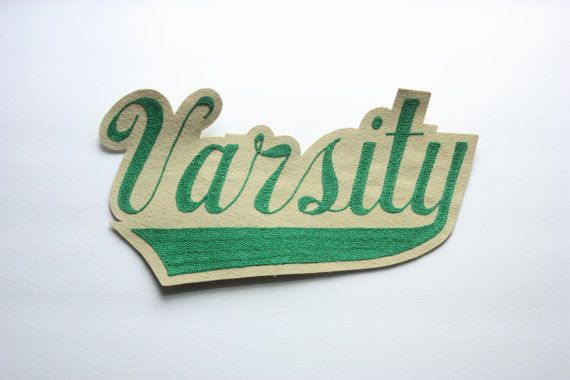 Vintage unused patch for letterman jacket or sweater that says Varsity in bright green on a beige background. Patch measures approximately 13