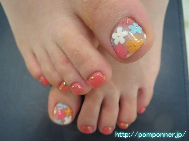 クリアベースにカラフルお花アートが可愛いフットネイル colorful flower foot nail art cute in clear base. The art of flower colorful clear base, thumb embellished with studs center. Claws of the other monochromatic painted in orange pink, I was decorated with studs the base.