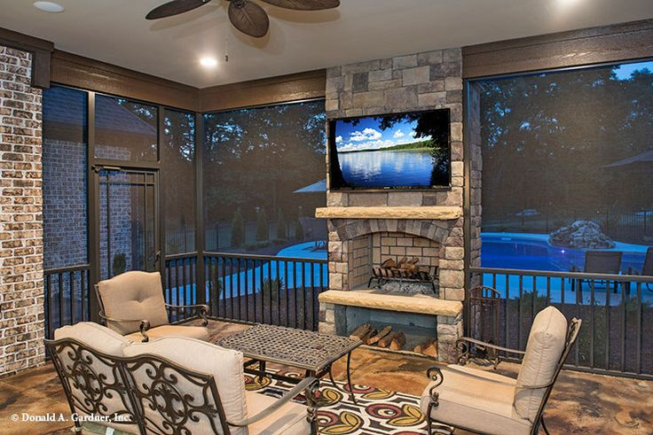 This screened porch is centered around the fireplace and overlooks the pool. The…
