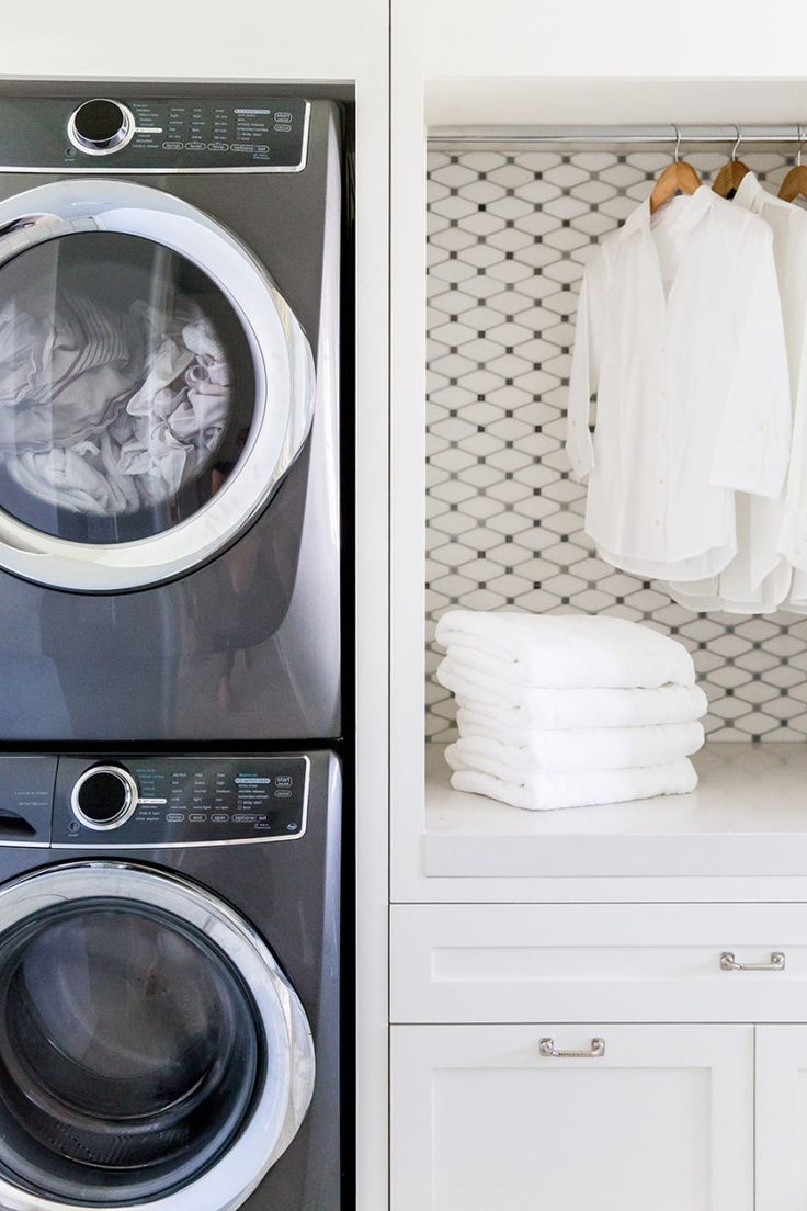 White and gray laundry room features a wall of stacked cabinets opening to  reveal a tension rod drying rack as well as White Carrara Grey Dot Marble  Diamond ...