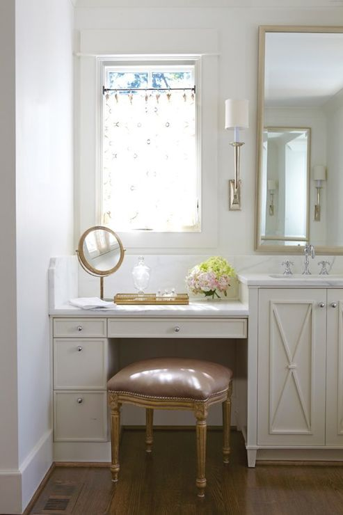 Pretty bathroom with a mauve velvet French vanity stool tucked below a built-in ivory dressing table accented with nickel pulls alongside white marble counters with a white marble backsplash under window dressed in cafe curtains. The dressing table butts up to an ivory sink vanity with x front cabinets illuminated by a champagne silver wall sconce beside the champagne silver vanity mirror.