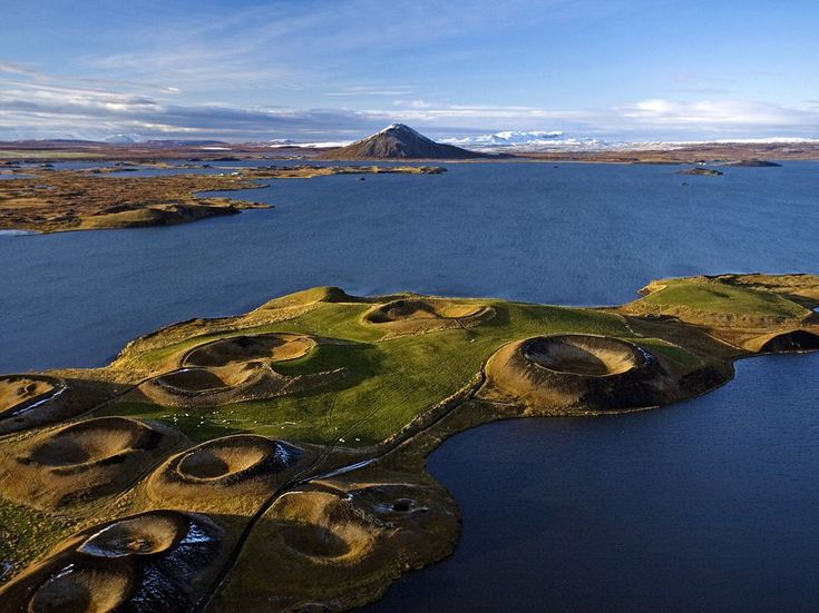 """Pseudo craters"" mark the land surrounding Lake Mývatn in Iceland. The southern part of the lake rests on a lava flow that was emitted 2,000 years ago. The pseudo craters are continually formed as water trapped beneath the Earth's surface turns to steam and explodes through the layer above. (Jonas Bendiksen)"