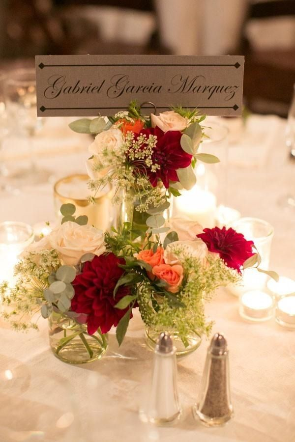 Red, pink and while dahlia and rose wedding centerpieces with author's names as table numbers.