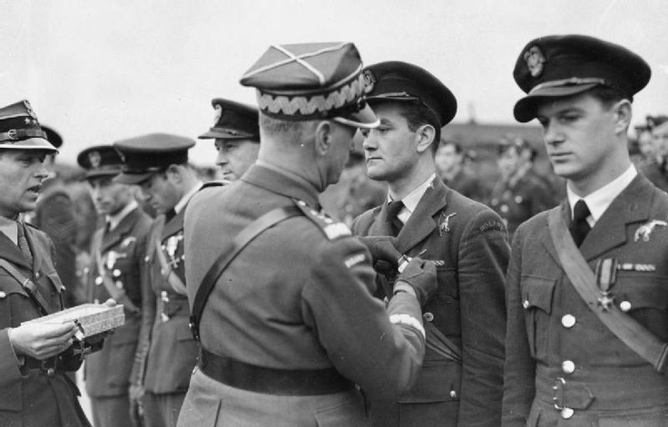 General Władysław Sikorski, the C-in-C of the Polish Armed Forces, decorating Pilot Officer Jan Zumbach of the 303 Polish Fighter Squadron with the Cross of Valour (Krzyż Walecznych). Zumbach is being decorated for shooting down his eleventh enemy plane. Pilot Officer Witold Łokuciewski, on Zumbach's left, awaiting his turn to be decorated. Both airmen are holders of the Distinguished Flying Cross, which ribbons are visible on their uniforms. 1941-10-29