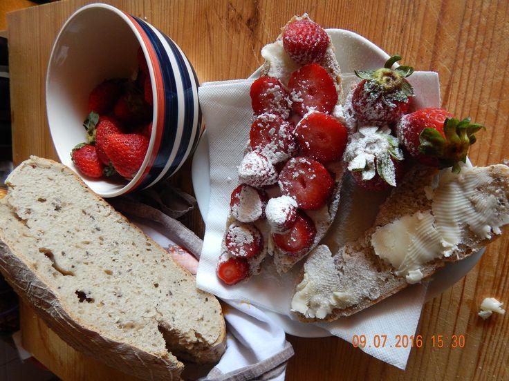Áji domácí chléb s máslem, nakrájené jahody a posypané moučkovým cukrem.... božská mana