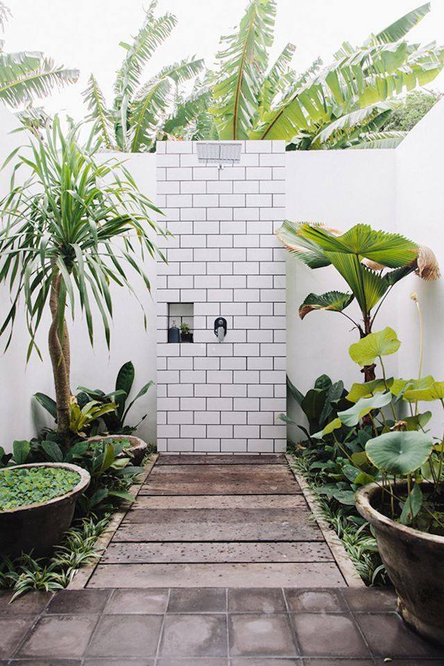 Modern outdoor shower with subway tiles, teak floor boards and tropical plants.