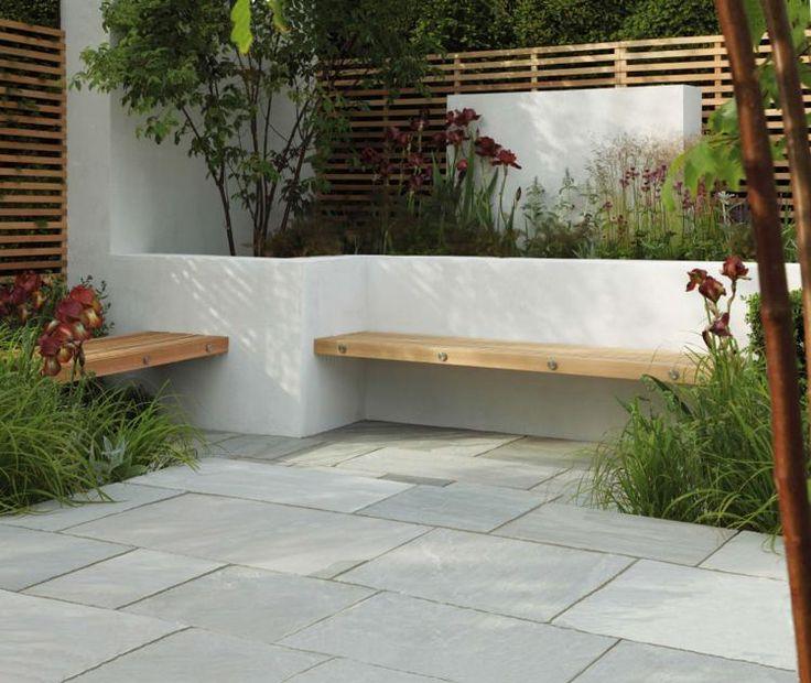 Strakke houten bank tussen plantenbakken in de tuin.