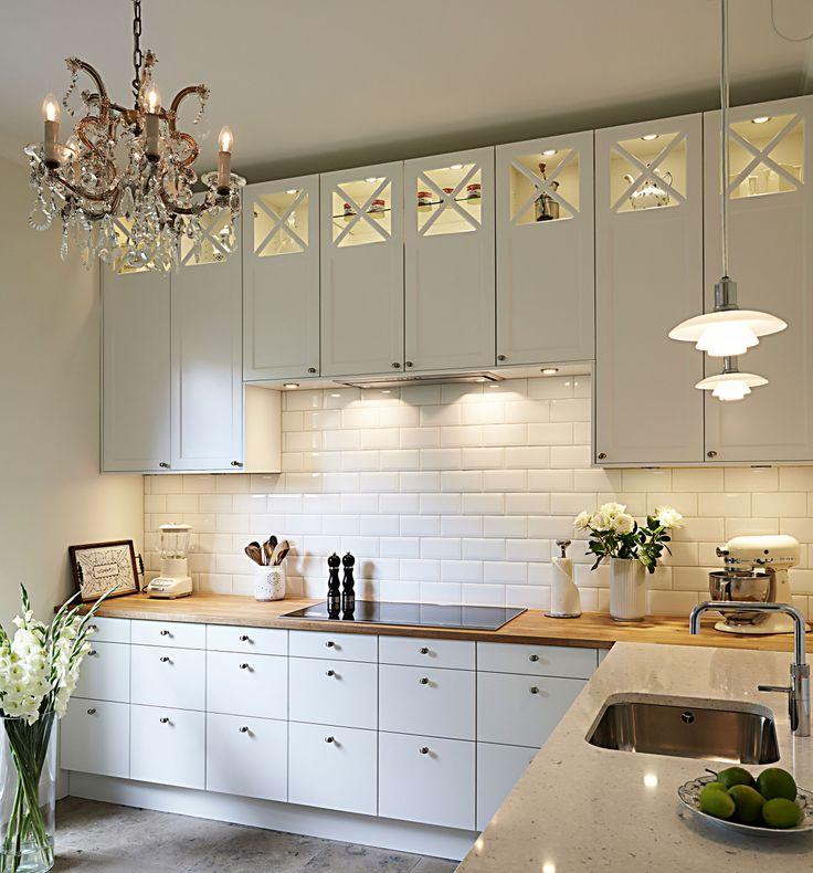 Moderne kombination af glatte og fyldnings fronter. Det emmer at stilfuld elegance. Bemærk igen lysekronen og de flotte PH lamper over køkkenvasken, som her er blevet sat sammen i køkkenet. Super flot.