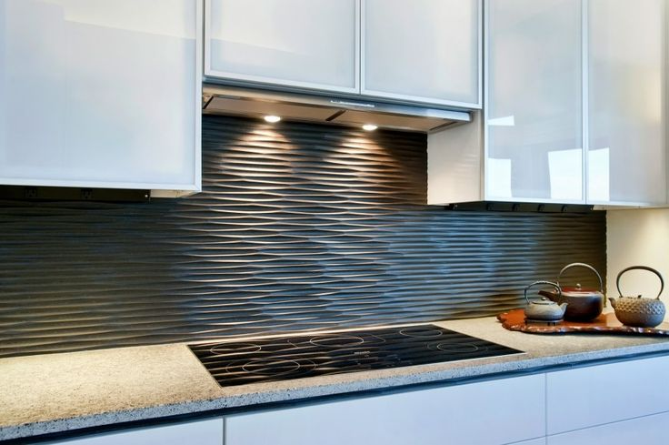 |Source: Sullivan Countertops  This wavy backsplash in graphite adds texture and interest to a white kitchen.