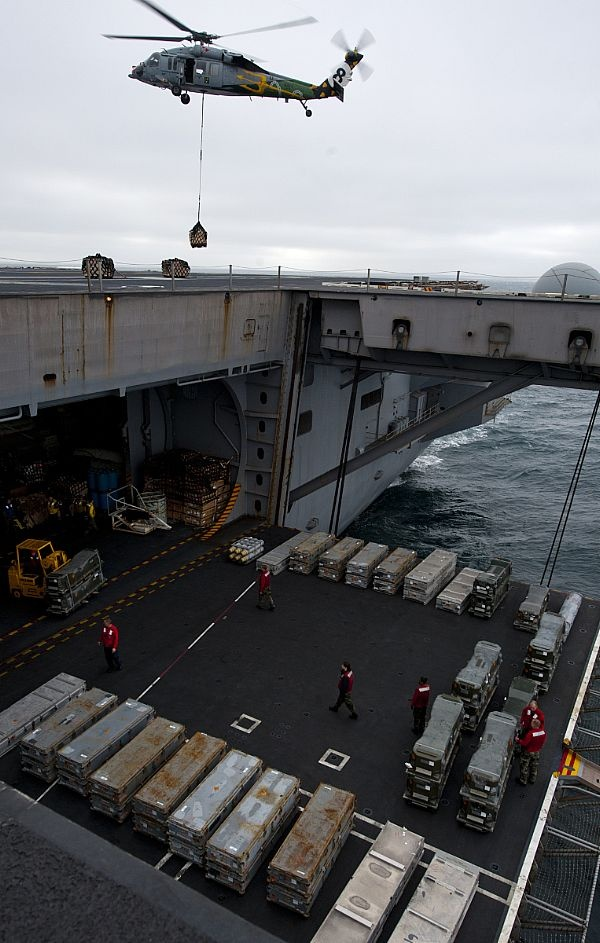 Sailors move ordnance on an aircraft elevator while an MH-60S Sea Hawk helicopter assigned to the Eightballers of Helicopter Sea Combat Squadron (HSC) 8 delivers ordnance on the flight deck of the Nimitz-class aircraft carrier USS John C. Stennis (CVN 74) during an ammunition on load. Stennis is conducting sustainment exercises off the coast of California designed to maintain mission readiness.