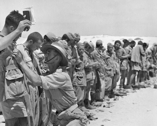 Italian prisoners of war being searched by a provost of the 9th Australian Divisional Provost Company