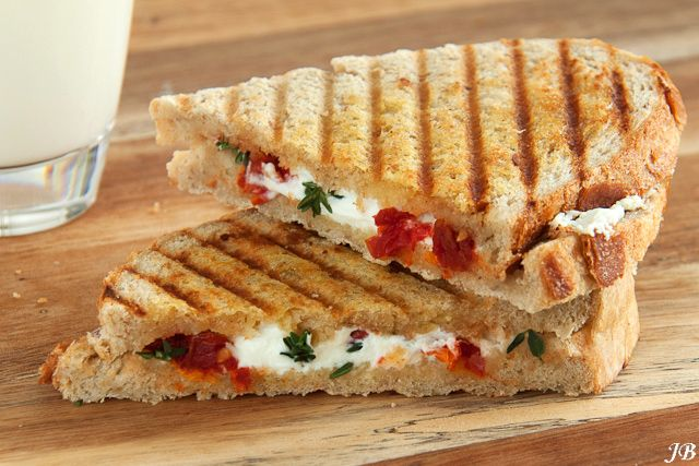 Ingrediënten: - 4 stevige boterhammen - boter - 100 g zachte geitenkaas - ongeveer 10 semi-zongedroogde tomaten, in reepjes gesneden - tijmblaadjes van 2 takjes - vloeibare honing Bereiden: 1. Bestrij