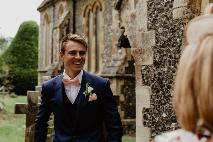 All smiles for the gorgeous groom, looking dapper in his navy suit with peachy bow tie and pocket square. Photo by Benjamin Stuart Photography #weddingphotography #groom #navysuit #bowtie #weddingday