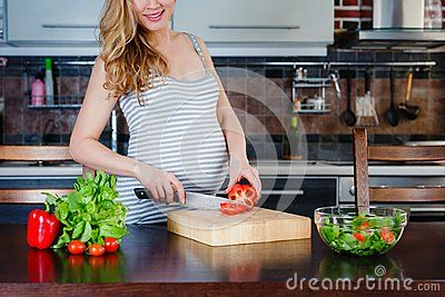 The Smiling pregnant woman in kitchen is cooking vegetable salad. Healthy food.