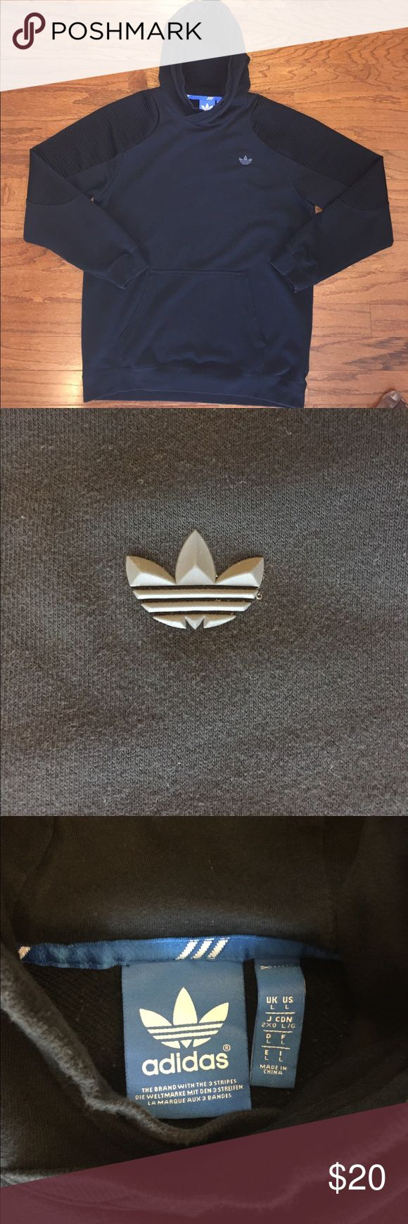 """Adidas Pullover Hoodie Sweatshirt Good condition, some normal wear, missing the drawstring, black color with a charcoal colored raised Adidas logo, textured polyester material on sleeves, main part made of 60% cotton and 40% polyester, sleeve inserts 100% polyester and hood lining 100% cotton, men's size large, measurements are about 23"""" pit to pit, 30"""" top to bottom and 25"""" shoulder to cuff. Great looking Hoodie...with a very unique design! Bundle for extra discount! adidas Shirts…"""