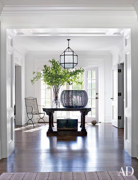 At the Connecticut retreat of Edie Parker accessories designer Brett Heyman and her family, decorator Mark Cunningham conjured a stylishly inviting atmosphere. In the entrance hall, a lantern by Suzanne Kasler from Circa Lighting hangs above the center table; the antique garden chair is from Bloom.