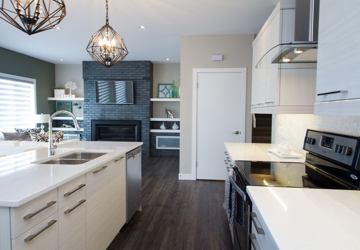 Neutral Galley shaped Showhome Kitchen with Pendant lighting and stainless steel fixtures.