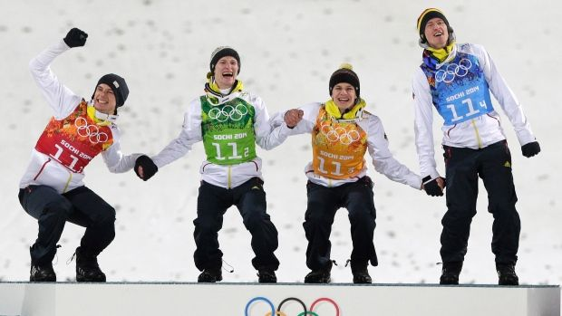 Germany's Andreas Wank, Marinus Kraus, Andreas Wellinger and Severin Freund, from left, celebrate on the podium after winning the gold medal during the ski jumping large hill team competition at the 2014 Winter Olympics on Feb. 17, 2014, in Krasnaya Polyana, Russia. (AP Photo/Matthias Schrader)