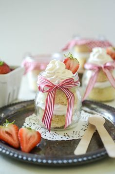 Mason Jar Tres Leches Cake made with Strawberry Whipped Cream and decorated with ribbon and gingham; perfect for summer BBQS.