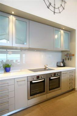 White cupboards with frosted glass inserts, downlights, glossy splash back