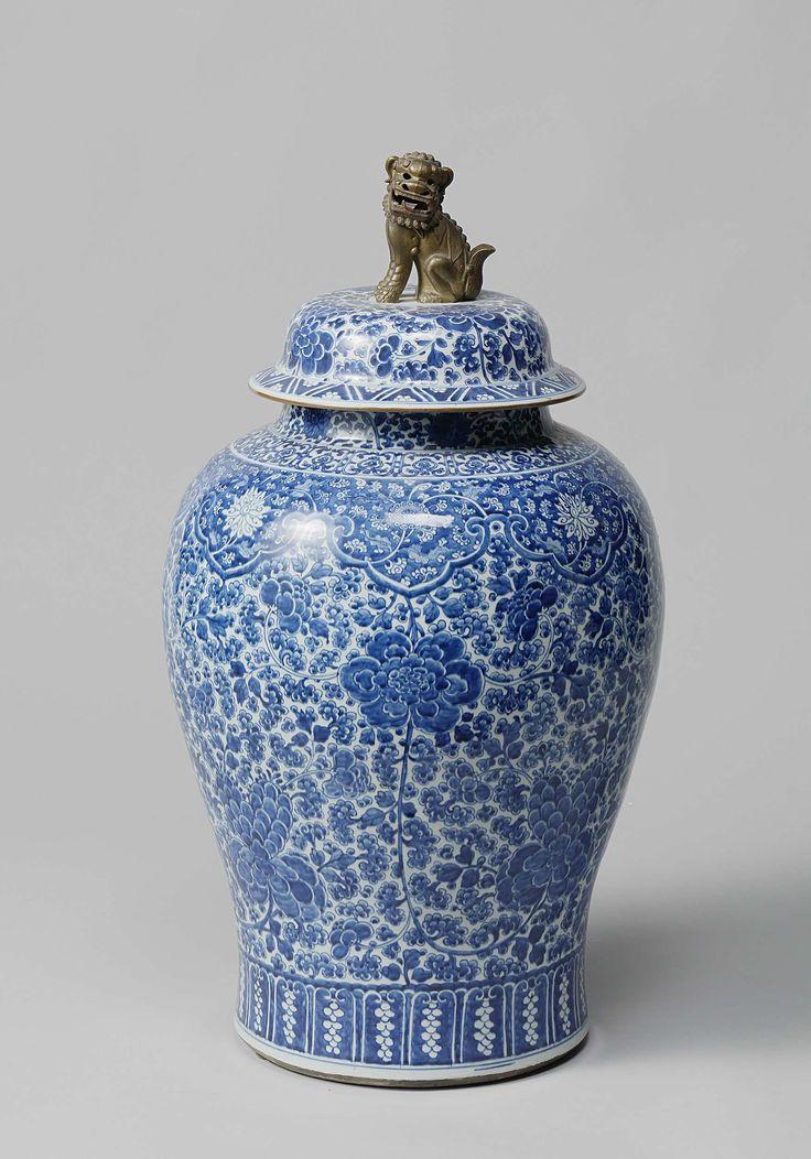Anonymous   Pair of lidded vases, Anonymous, c. 1700   Grote vaas met deksel; breed van boven en naar beneden verjongend; korte ronde hals en een gewelfde deksel met vlak, schuin naar beneden uitstekende rand en vlakke bovenkant, met een verguld leeuwtje met rode tong en zwarte ogen als knop. De vazen zijn zeer dicht versierd met ranken en bloemen in onderglazuur blauw. Boven de witte voetrand een brede strook in ondergalzuur blauw, waarin hangende druiventrossen zijn uitgespaard. Onder de…
