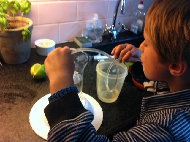 Proefje: hoe komt het water van de ene in de andere kan, zonder de kannen aan te raken?