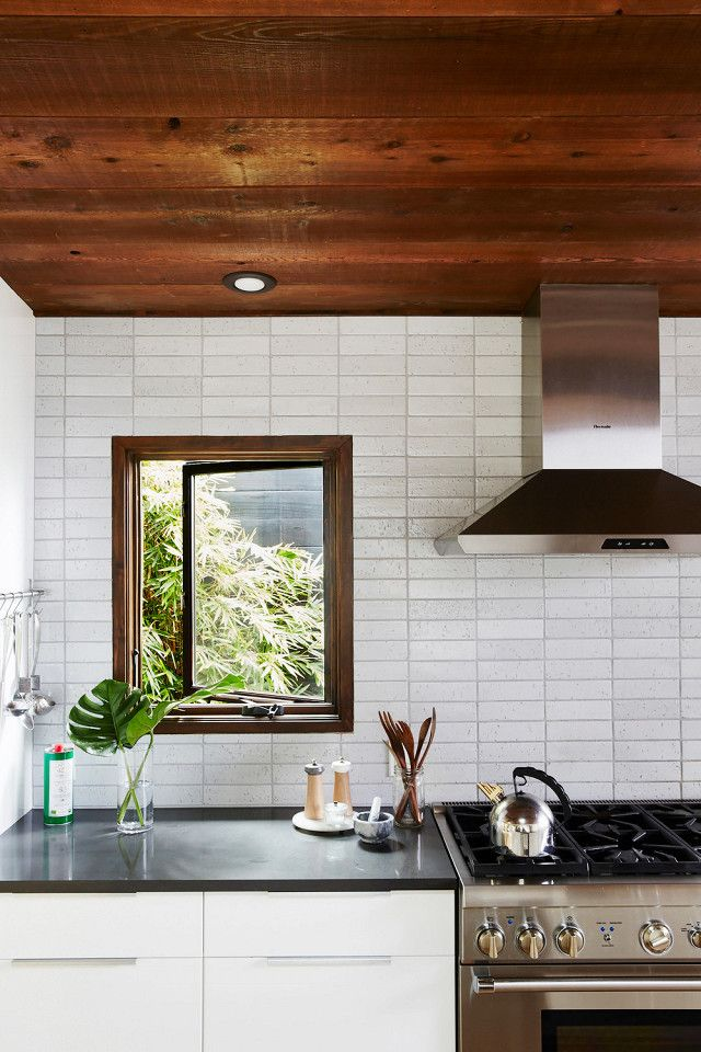 Cozy kitchen with Oak ceilings, subway tile backsplash, and a stainless steel stove