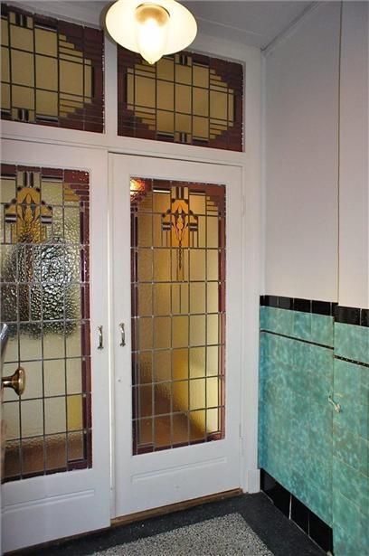 Glas in lood deuren en groene tegels met zwaarte bies en rand in de hal van deze jaren '30 huis in Haarlem