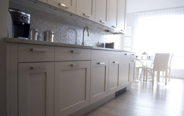 Simple and elegant, this shaker style white kitchen will always be in style and will compliment any decor.  Brushed nickel hardware on cabinets.