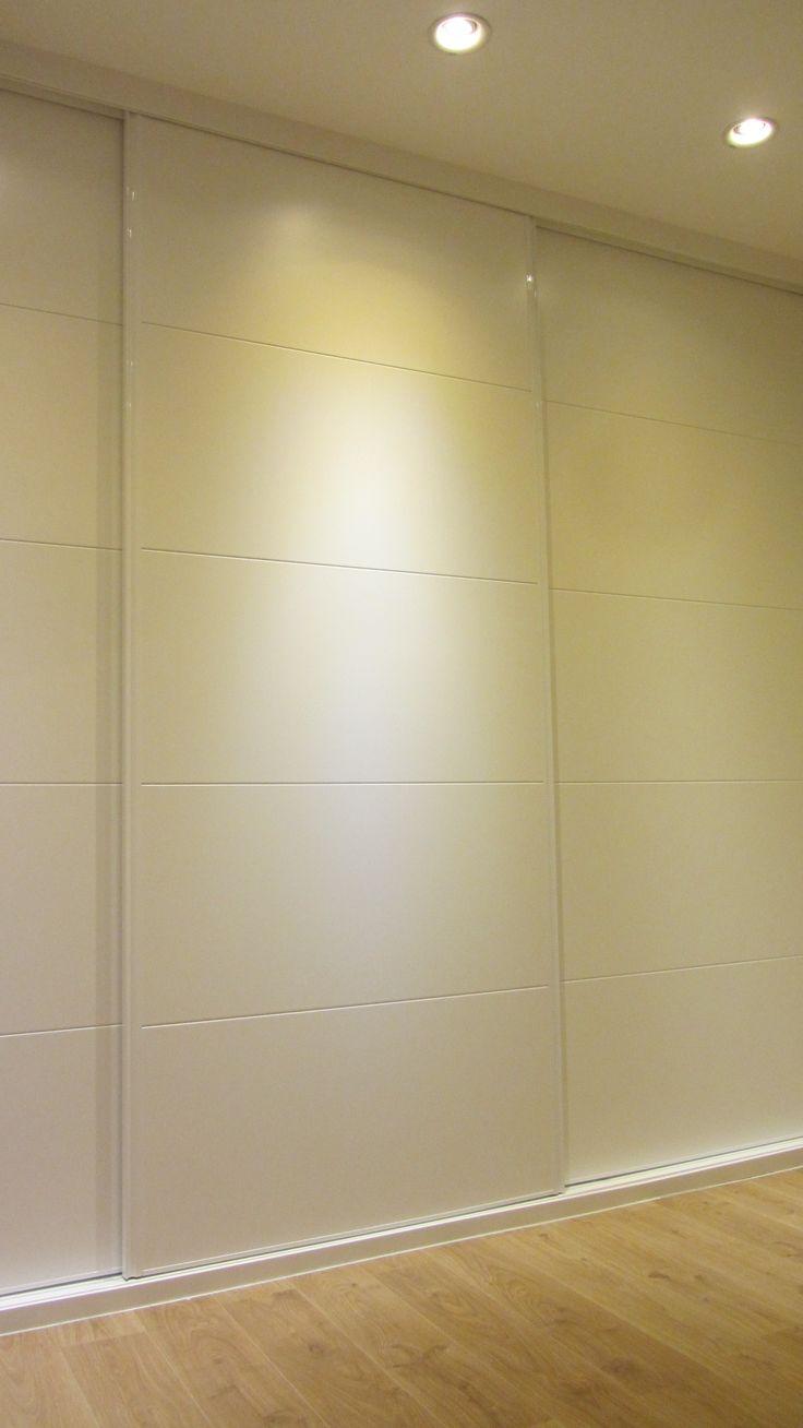 Detalle de armario de dormitorio principal, de tres puertas correderas lacadas en blanco, con decoración de franjas tipo pico de gorrión.