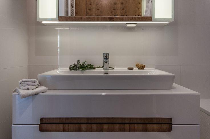 Biała łazienka ocieplona drewnem.