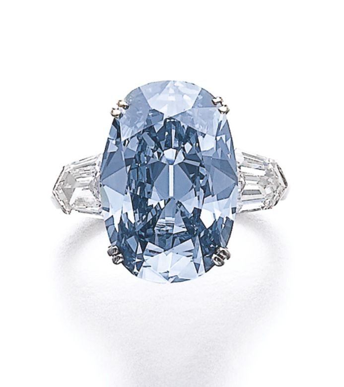 Magnificent fancy deep blue diamond ring Set with an oval fancy deep blue diamond weighing 7.74 carats, between shield-shaped diamond shoulders, size 51, maker's mark for Jacques Timey.