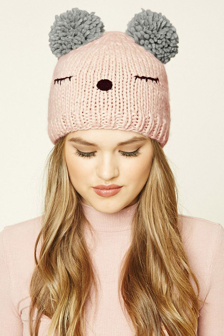 A ribbed knit beanie featuring a stitched sleepy face and pom-pom ears.