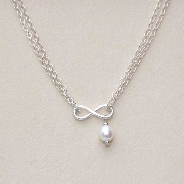 An elegant minimalist design entirely in sterling silver. A translucent pearl hangs from a dainty infinity focal accent set on a double strand of sterling silver link chain creating a very understated graceful design.  Finished with a 4cm extension chain with a dainty open heart drop.  Eternal is so versatile, it will go with anything and looks great with everything. Wear it alone or layered with other necklaces.