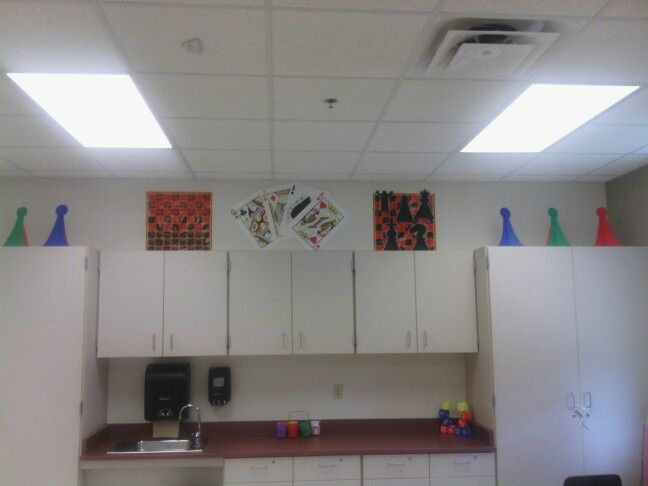 Top of classroom cabinets. Checkerboard/Chess Boards purchased at Dollar Tree. Checkers glued on. Chess pieces hand drawn and glued on. Large playing cards purchased at party supply store and large game pieces hand drawn and attached to small plastic traffic cones.