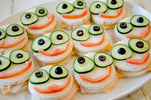 …Monster Sandwiches (American cheese and deli turkey sandwiched between crustless bread cut out from a round cookie cutter, topped with cucumber and black olive eyes and tomato mouths)…