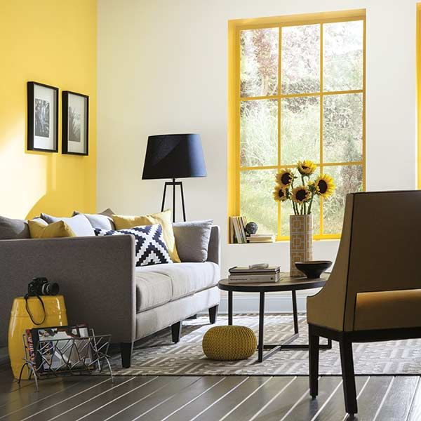 A painted window frame picks up a living area's yellow accent wall and accessories. Sherwin-Williams's Decisive Yellow.