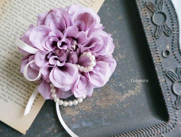 とても綺麗な薄紫色をしたダリアにユリアパールを合わせた上品なコサージュです。ネックレス無しでもこれだけでシンプルに上品&華やかになります。入学式、卒業式などのフォーマルスーツにはもちろん、結婚式やパーティ、発表会のドレスなどにも合わせて頂けます。金具はクリップとピンの2way(写真4枚目)ですので、お洋服だけでなく、帽子やバッグ、髪飾りとしてもお使い頂けます。お花はアーティフィシャルフラワーを使用しています。アーティフィシャルフラワーとは、生花をリアルに再現したポリエステルやワイヤーなどで作られた高品質な造花です。実際の色になるべく忠実に撮影しておりますが、若干の色合いの誤差はご了承ください。保管に便利なコサージュケースにお入れしてお届け致します。使用造花 : ダリアサイズ : 長さ約10㎝ × 幅約10㎝ × 厚み約5cm(リボンを含まない大きさ)『春色新作ハンドメイド2018』『新生活ハンドメイド2018』『母の日ハンドメイド2018』