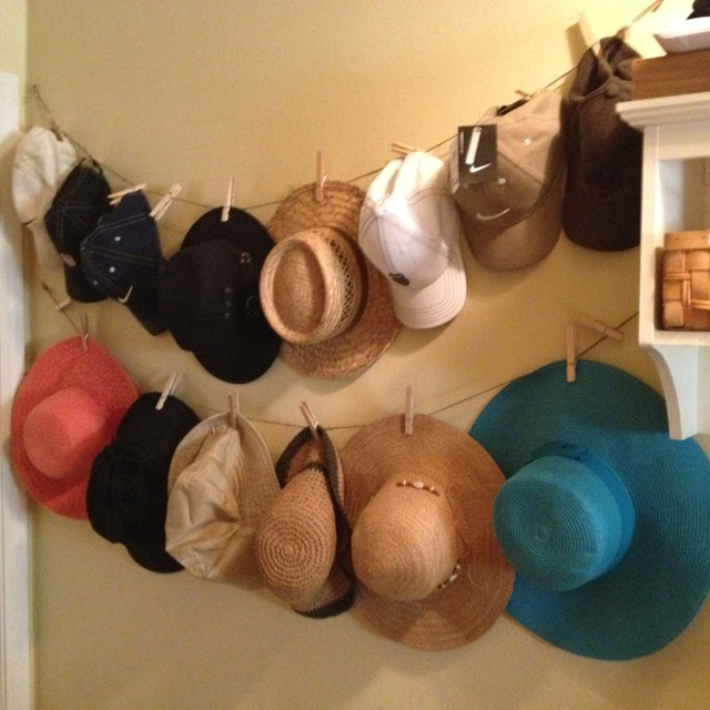 Hat organization: I struggled to find a way to keep all our hats organized until I came up with this idea! I strung two cotton ropes across my available wall space, securing it with pushpins. Then just hung up the hats using clothespins. This is right by our back door, making it easy to grab a hat on the way out! My husband even remembers to hang his hat back up when he comes in!