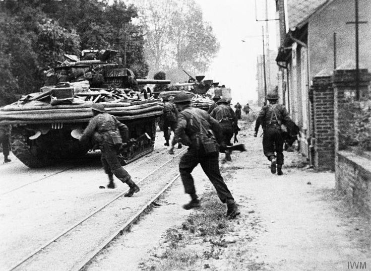 Sherman DD tanks of 'B' Squadron, 13th/18th Royal Hussars support commandos of No. 4 Commando, 1st Special Service Brigade, on the Rue de Riva-Bella as they advance into Ouistreham, Sword Area.