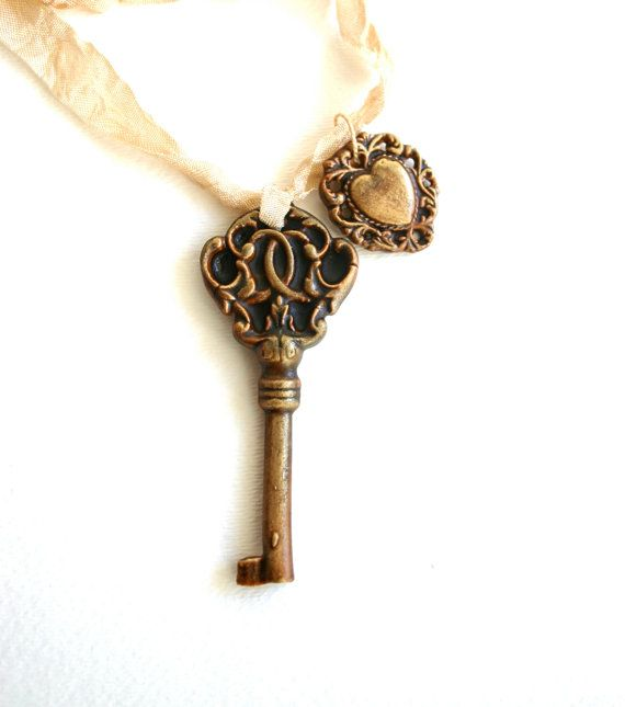 """Skeleton Key necklaces are crafted, by hand, from an antique key dating back to the early 1800's. Each key is given an edible patina and detailed to perfection. Each necklace comes with 20"""" of silk ribbon. This Candy Necklace comes with an additional candy filigree heart charm. Both the Key and Heart Charm are chocolate candy."""