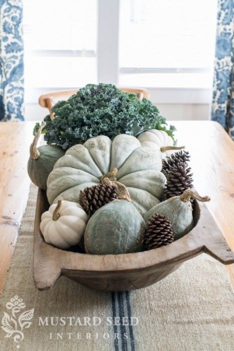 Fresh kale, blue Cinderella's pumpkin, blue hubbard squash, mini white pumpkins, and pine cones in a dough bowl.