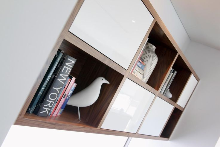 Custom Wall Hung Bookcase. This piece was designed for Craig Shieles homes. With American black walnut and glass white door features. This piece can be custom made to suit your needs and requirements.