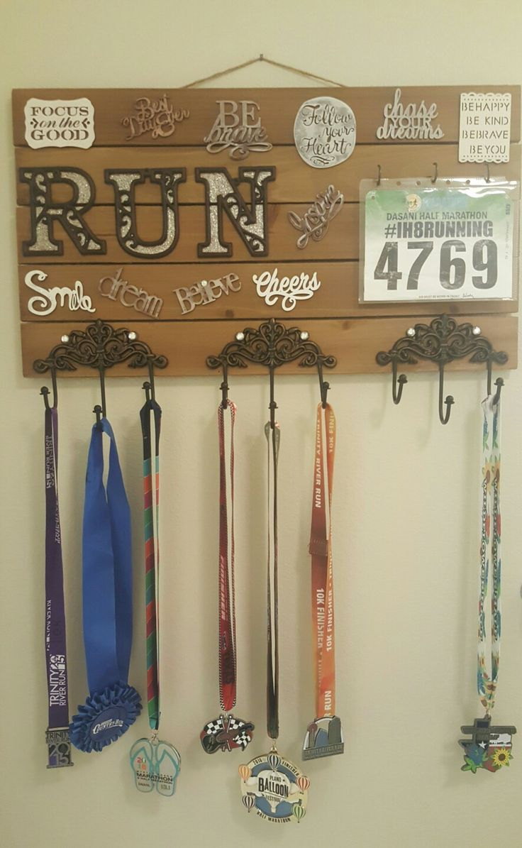 """DIY medal display Purchased sayings, board, and small hooks at Michael's craft store and the medal holders at Hobby Lobby. For the race bibs, I used 5.5""""x8.5"""" page protectors. Used scrapbook rhinestones to cover screws with glue dots. Final touch was adding glitter paint inside the RUN letters."""