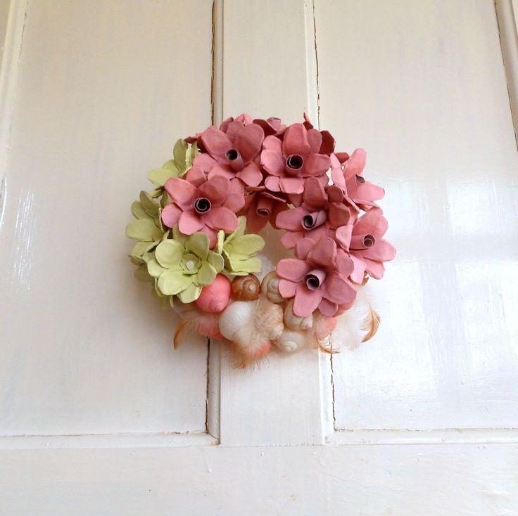 Věneček s ulitami Dekorační, růžovo zelenkavý věneček, doplněný ulitami a peříčky, ve stylu Shabby Chic. Růžičky jsou vytvořené z kartónů na vajíčka, ručně barvené nezávadnou vodorozpustnou barvou. Ulity jsou pečlivě vyčištěné, vyvařené a nalakované. Průměr věnce je 25cm. Je velice dekorativní a úžasně doplní váš interiér. Věneček může zdobit ...